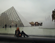 Seizing a a rare uncrowded moment to strike a pose at the famous pyramid outside the Louvre museum.